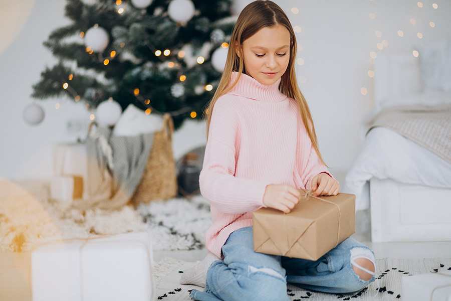 Girl opening a gift on Christmas Day